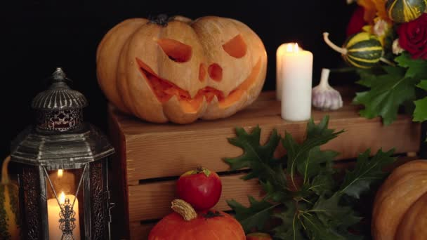 Dýně, svíčky, lucerny a další halloween atributy u stolu jako Halloween pozadí. Nekonečné video podzimní slavnostní výzdoby u dřevěného stolu. Halloween téma a jeho symboly.