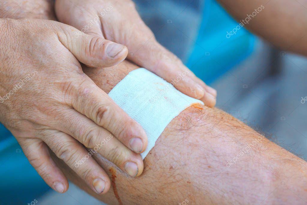 process of applying a bandage on the injured leg