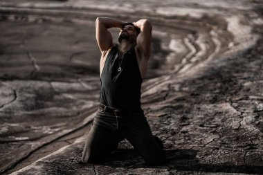 Attractive tanned man on the black sand