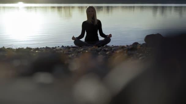 Yoga-Frau bleibt am Flussufer und meditiert.