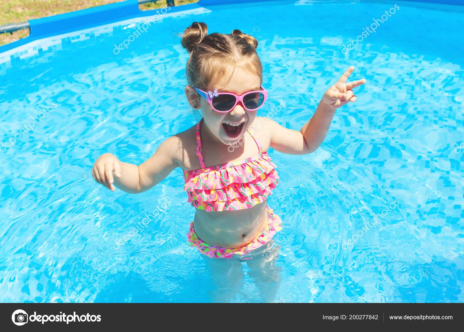 a95a7e33c5623 Nette und lustige kleine Mädchen im Schwimmbad, Schwimmen im Pool schwimmen  Ring, Brille Sonne und Spaß. Sommer-Lifestyle-Konzept — Foto von paninastock