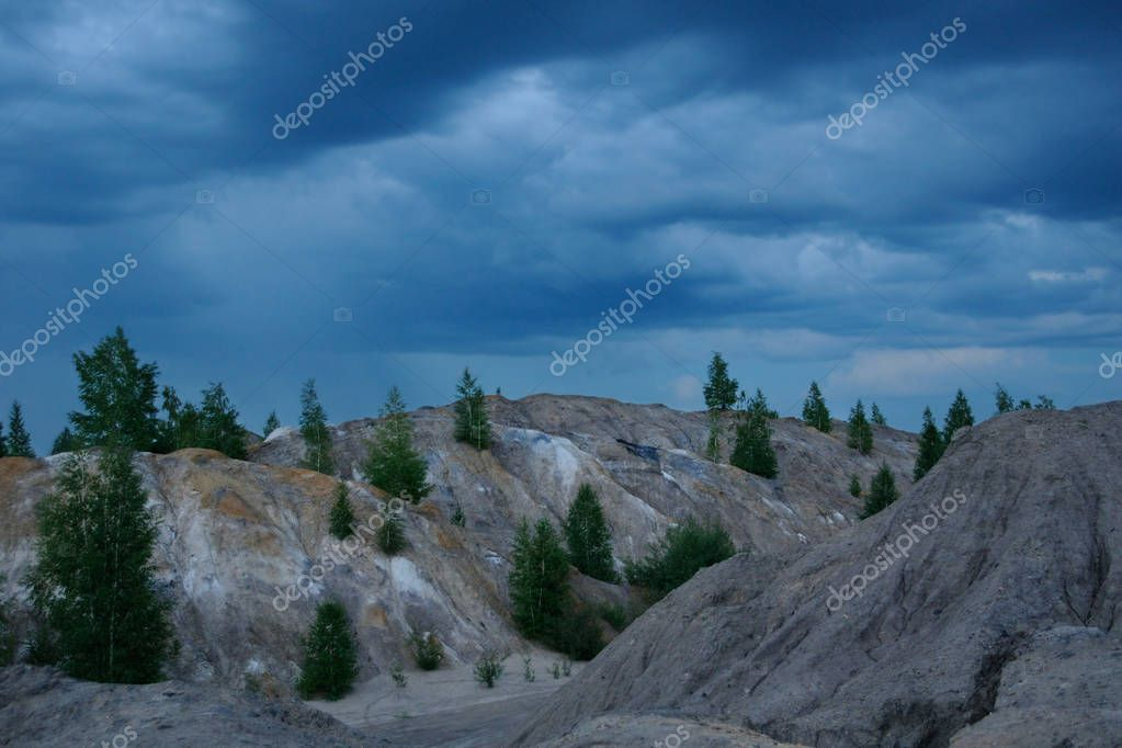 Rain is approaching bare hills of the former brown coal open cast, Ushakov open pits, Tula region, Russia