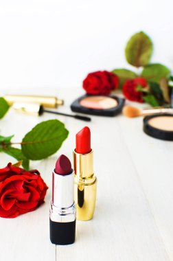 Various cosmetic products for make-up with red roses on a white wooden background with copy space. Makeup Accessories Red lipstick Selective focus. Women's things