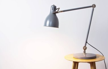A gray table lamp in the interior against a white wall. The concept of business or education with a place for your text. Detail of interior minimalism background.