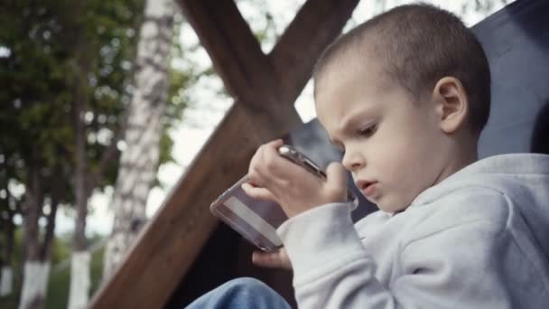 boy of two years sitting on a bench in the park and watching cartoons on a smartphone