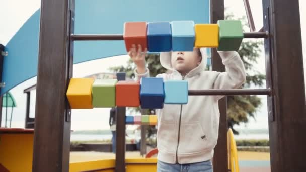 boy playing cubes on the playground.