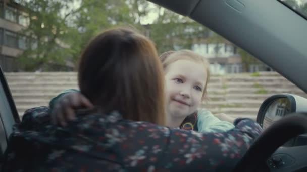 anya ül az autóban, és kísérőik lányát az iskolába