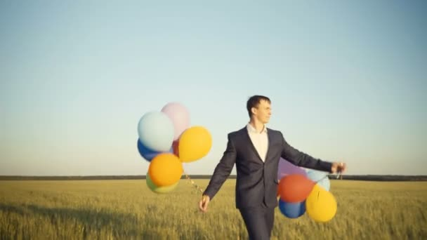 creative businessman walk at a field holding colorful balloons.