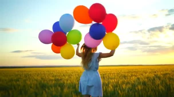happy woman with balloons running in the wheat field at sunset