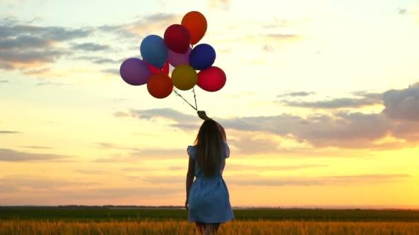 šťastná žena s balóny, které jsou spuštěny v poli pšenice při západu slunce