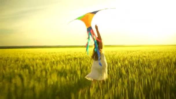 Mädchen läuft mit Drachen auf dem Feld herum.