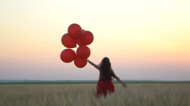 happy girl with balloons running in the wheat field at sunset.