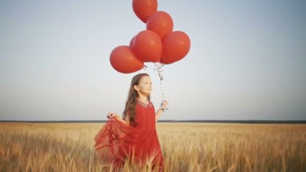 boldog fiatal lány fut a búzamező napnyugtakor léggömbök