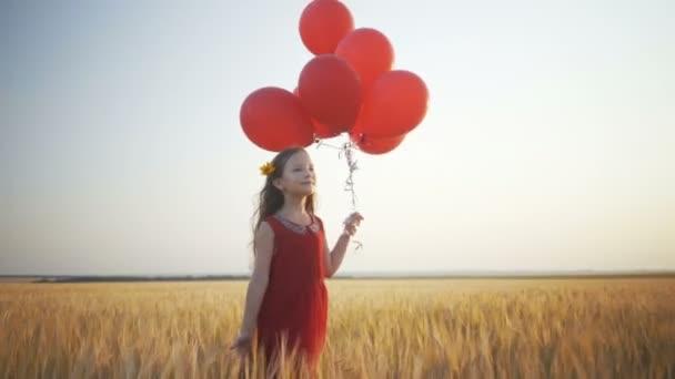 šťastná mladá dívka s balóny, které jsou spuštěny v poli pšenice při západu slunce