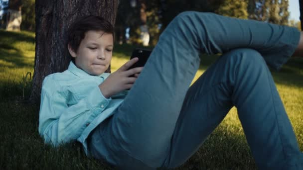teenager playing video games on his smartphone outdoors.