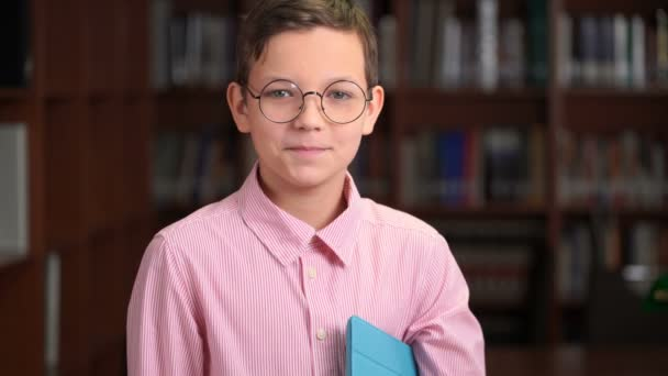 portrait shot of the cute schoolboy with tablet and standing near the bookshelf in the library