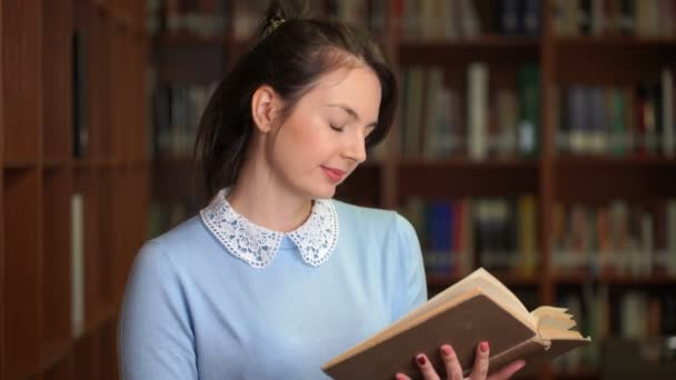 portrait of smiling beautiful pretty woman with book in library office bookshelf background