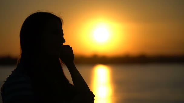 Woman listening to music with headphones on the sunset background.