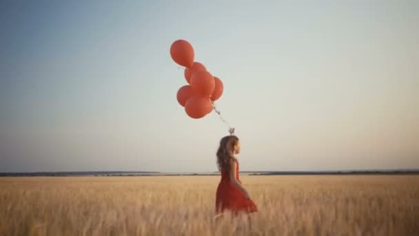 happy young girl with balloons running in the wheat field at sunset. 4k video.