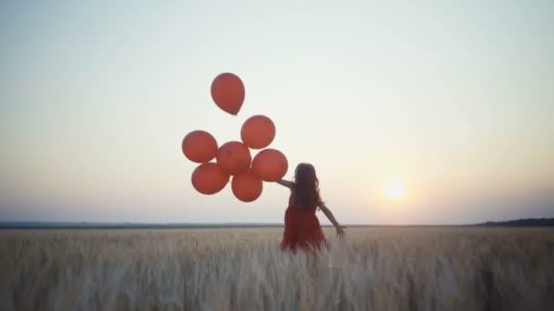 šťastná mladá dívka s balóny, které jsou spuštěny v poli pšenice při západu slunce. 4k video.