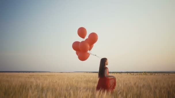 boldog fiatal lány futás a búzamező napnyugtakor léggömbökkel. 4k videóinak.