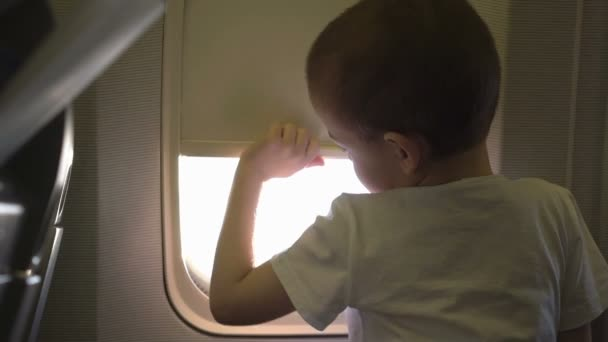 kleiner süßer Junge sitzt auf dem Sitz und öffnet Flugzeugfenster