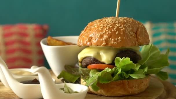 Domácí Burger se smaženou bramborami a omáčkami na dřevěném tácku