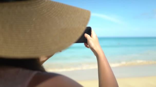 junge Frau mit Hut fotografiert mit Smartphone am Strand des Ozeans