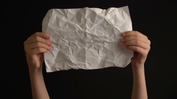 Ruce držící zmačkaný papír