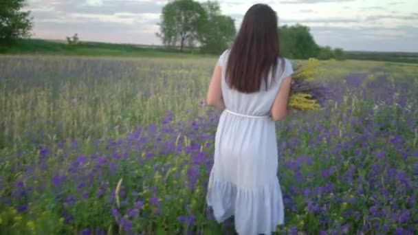 Young Woman Walking With Bouquet of Field Flowers.