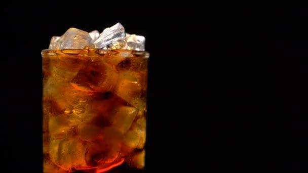 Cola mit Eis und Blasen im Glas drehen sich auf schwarz