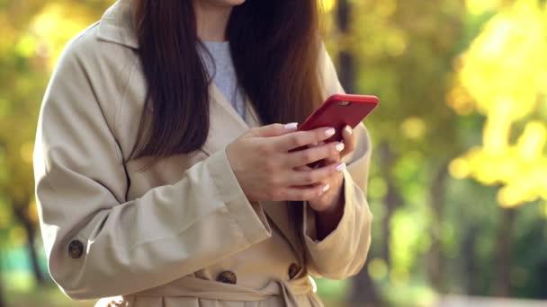 Junge Frau im Mantel oder Trench mit Smartphone im Herbstpark