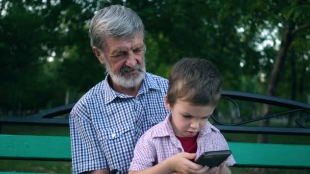 Senior grandfather and grandson are sitting on a bench in the park and playing on a smartphone
