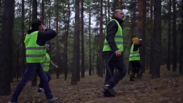 zöld mellényes önkéntesek egy csoportja eltűnt személyek után kutatott egy fenyőerdőben.