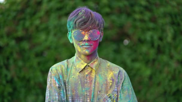Portrait of boy standing being covered in coloured powder at holi festival