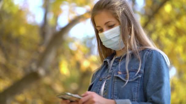 Portrait Frau in Schutzmaske geht auf die Straße verwendet Telefon-Textblätter surft die Internet-Suche Nachrichten der zweiten Welle covid-19 Coronavirus Schutz Pandemie