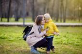 Roztomilé malé dítě hraje v jarní nebo letní parku. Preschooler kid s žlutá kytice. Batole chlapec dává jeho maminka čerstvých divokých květů. Mladá matka a její malý syn dohromady