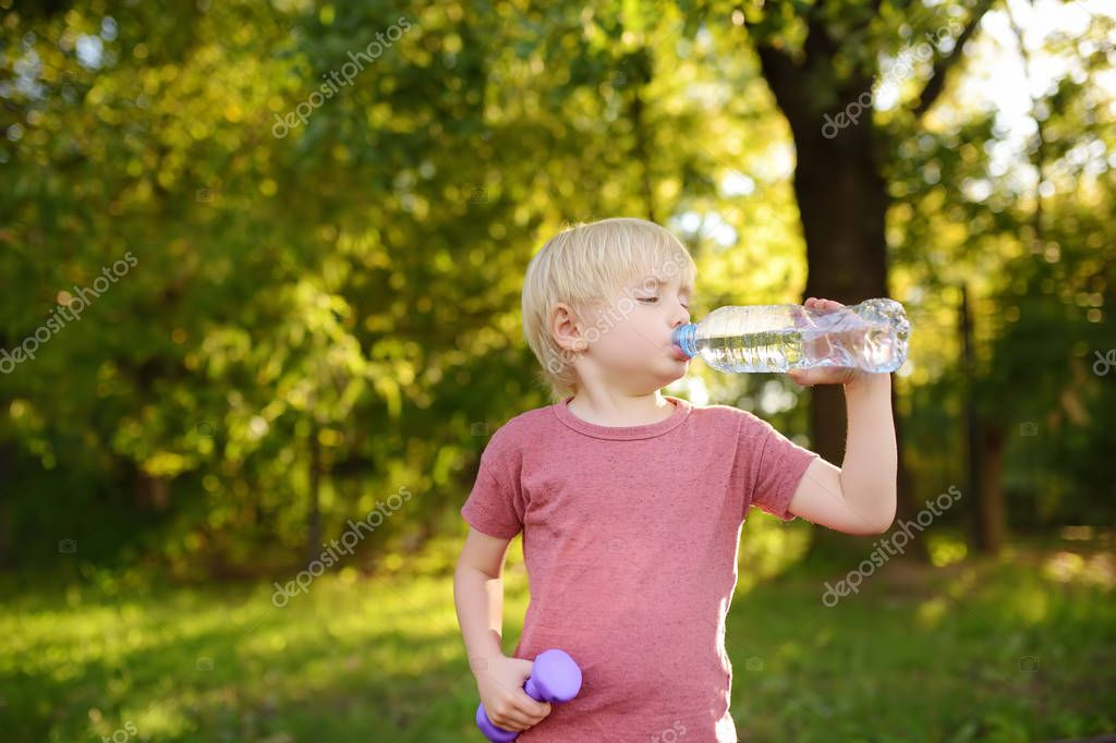 Little boy drinking water during workout with dumbbells. Children's sport.