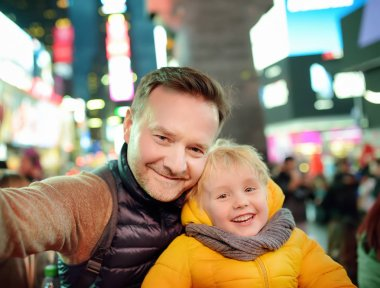 Little boy and his father taking selfie on Times Square in evening, downtown Manhattan. Famous street of New York City.