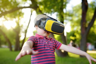 Little boy using virtual reality headset outdoor. VR, VR glasses, augmented reality experience. Kids and modern technology, innovation.