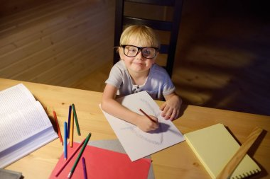Little boy wearing glasses doing homework, painting and writing at home evening. Preschooler learn lessons - draw and color image. Kid training to write and to read. Child education concept.