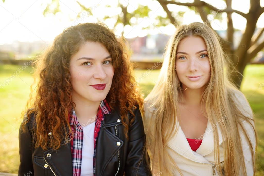 Outdoors portrait of two delightful young woman. Variety of female beauty.