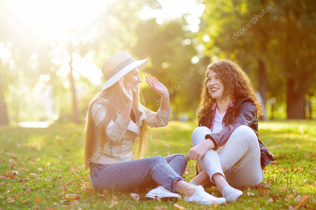 Outdoors portrait of two delightful young woman. Variety of female beauty. Two caucasian girls friend stroll together in sunny day