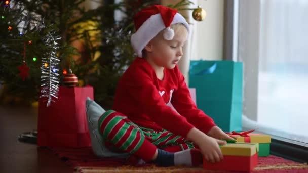 Netter kleiner Junge mit Weihnachtsmütze, der ein Weihnachtsgeschenk öffnet. glückliches Kind am Weihnachtsmorgen. gemütliches Wohnzimmer mit geschmücktem Tannenbaum und Lichtern