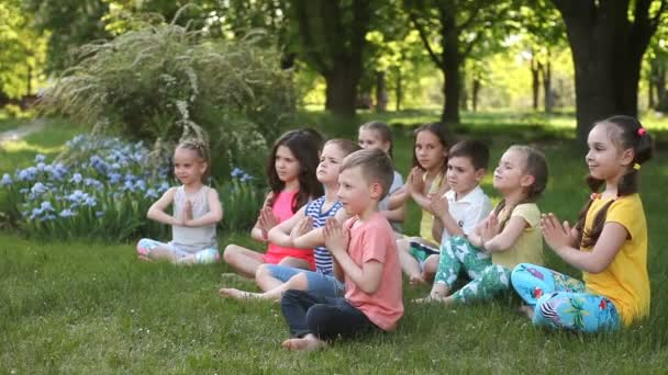 Happy children are doing yoga in the Park sitting on the grass