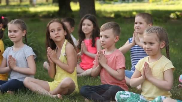 Šťastné děti dělají jógu v parku sedět na trávě