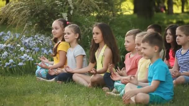 Glückliche Kinder machen Yoga im Park im Gras sitzend