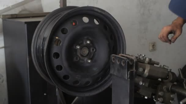 Meccanico di automobile che ripara auto ruota dellautomobile alla stazione di servizio di riparazione