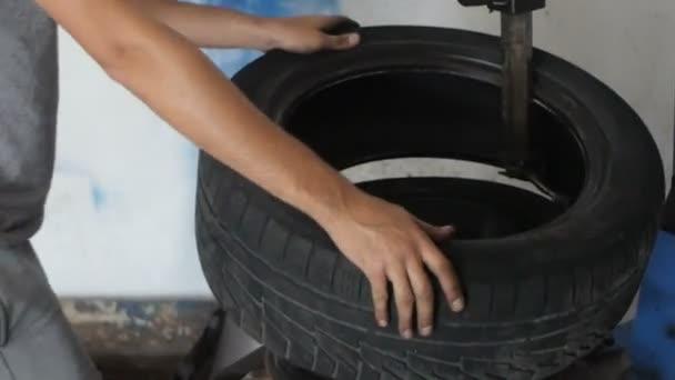 Auto mechanik opravuje auto kola automobilu v servisním centru