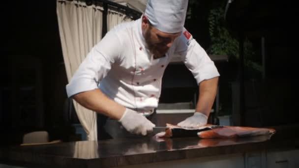 Kuchař vyřezává čerstvý losos v restauraci